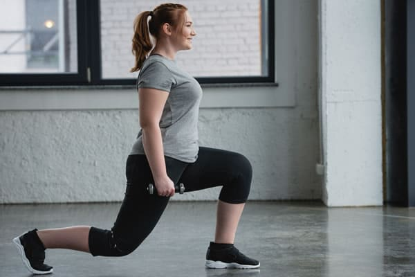 Plus size girl doing lunges for the perfect butt