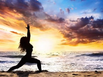 Woman doing yoga pose on beach