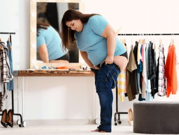 plus size woman trying on a pair of skinny jeans