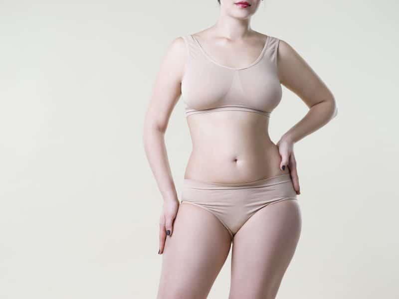 Woman in beige underwear on studio background, cellulite on female body