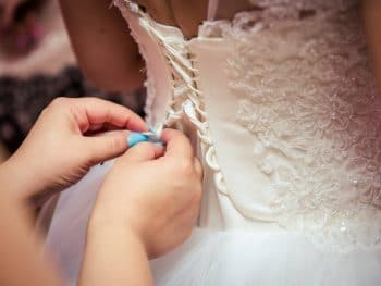 photo-of-woman-fixing-the-wedding-gown