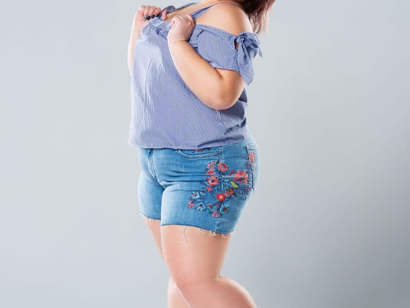 Plus size fashion model in jean shorts woman on gray background