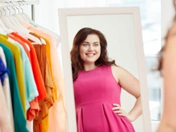 happy plus size woman posing at shopping mall mirror