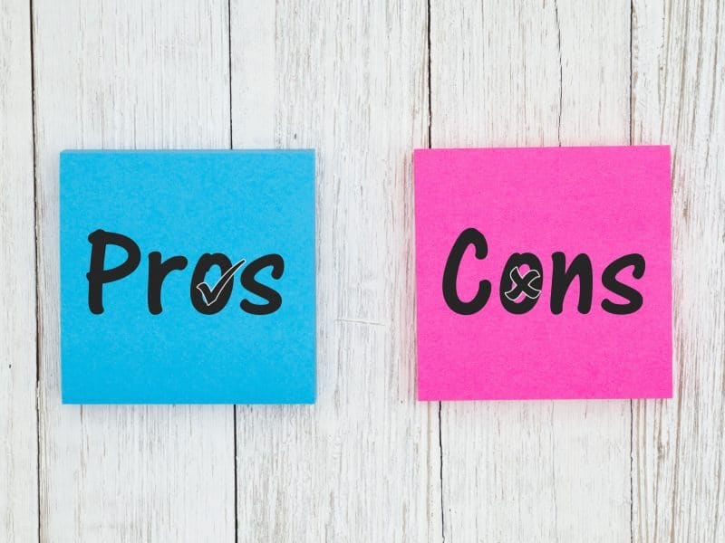 Pros and Cons on two sticky notes on white wood