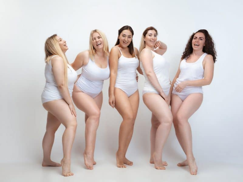 Portrait of beautiful plus size young women posing on white background
