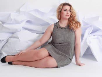 Plus size woman sat down in grey dress