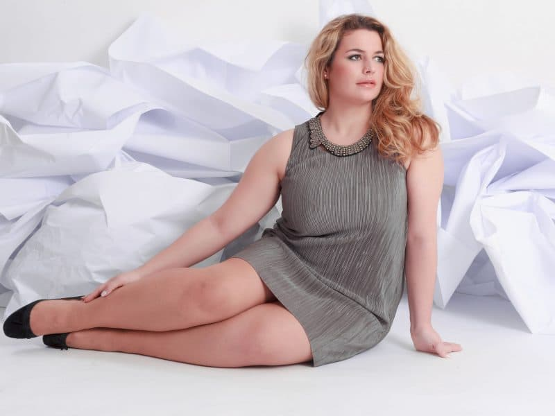 Plus size woman sat down in grey dress